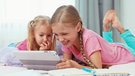 Sisters-Using-Tablet-PC-When-They-Are-In-The-Bedroom