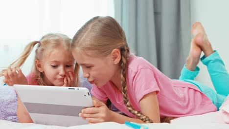 Sisters-Using-Tablet-PC-Lying-On-The-Bed