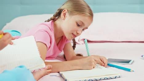 Dos-Hermanas-Están-En-La-Cama-Y-Algo-Dibujando-En-Sus-Cuadernos