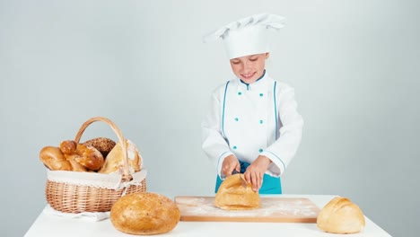 Young-Baker-Girl-Cutting-Loaf-Of-Bread-And-Gives-You-One-Piece-Looking-At-Camera