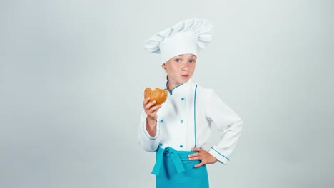 Young-Baker-Girl-Eating-Small-Bread-Looking-At-Camera-Isolated-On-White