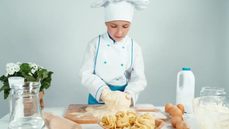 Young-Baker-Girl-Making-Dough-At-The-Kitchen-Table-And-Smiling-At-Camera