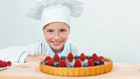 Young-Baker-Looking-At-Chocolate-Cake-With-Fruits-Raspberries-And-Blueberries