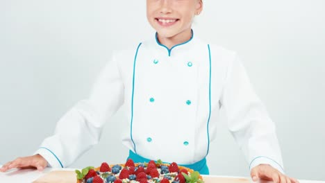 Young-Chef-Baker-Examines-Chocolate-Cake-With-Sweets-And-Fruits