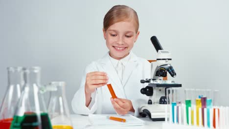Young-Chemist-Holding-Test-Tube-And-Smiling-At-Camera
