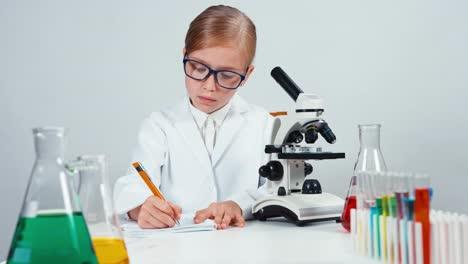 Joven-Químico-Niña-De-La-Escuela-7-8-Años-Algo-Escrito-En-Su-Cuaderno