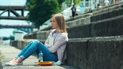Junge-Frau-Die-Ihre-Bücher-Hält-Und-Am-Stadtkai-Sitzt-Und-Mit-Lächeln-Schaut