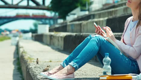 Young-Woman-Using-Your-Cell-Phone-And-Looking-With-Smile-At-Camera