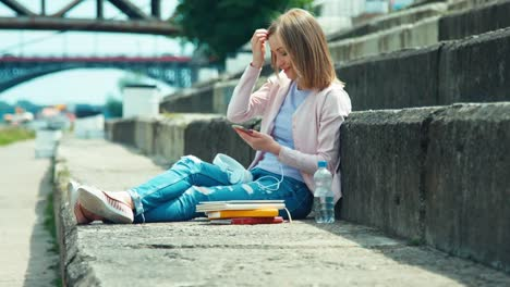 Young-Woman-Using-Your-Cell-Phone-Outdoors-Sitting-On-City-Quay