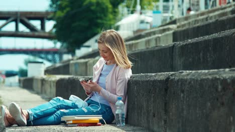 Young-Woman-Using-Your-Cell-Phone-Outdoors-Sitting-On-City-Quay-Near-Her-Book