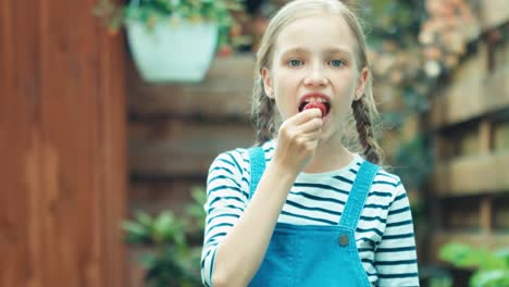 Child-Girl-Eating-Strawberry-And-Smiling-At-Camera-In-The-Kitchen-Garden