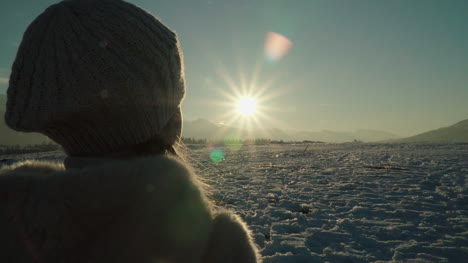 Child-Girl-Hands-Make-Heart-Around-Sun-At-Sunset-In-Mountains-In-Sunny-Winter