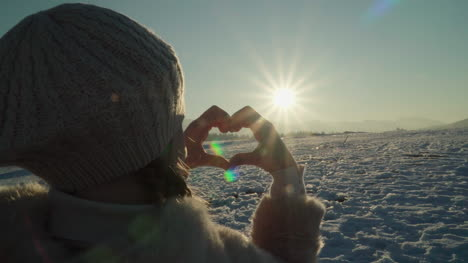 Girl-makes-a-heart-with-her-hands-at-sunset-1