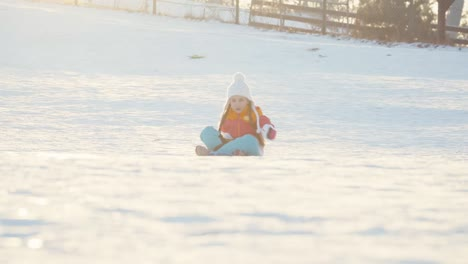 Child-Girl-Rides-A-Sledding-Down-On-Snow-Disk-A-Winter-Hill-Girl-Laughing