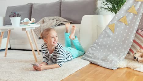 Child-Girl-Using-Cell-Phone-Sitting-On-The-Carpet-Smiling-At-Camera
