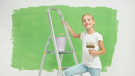 Child-Holds-Paint-Brush-Standing-Near-Ladder-And-Against-Green-Screen