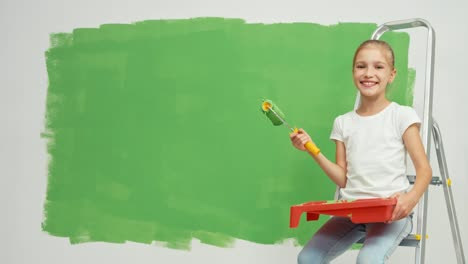 Child-Holds-Paint-Roller-And-Smiling-At-Camera