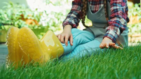 Child-In-Rubber-Boots-Touching-Grass