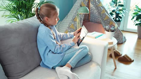 Child-Is-Online-With-Tablet-PC-And-Smiling-With-Teeth-At-Camera-Top-View