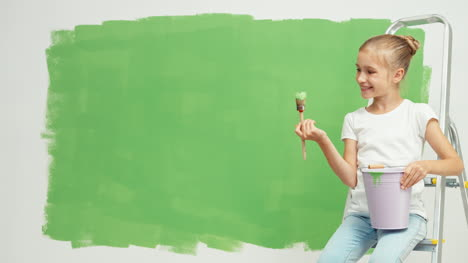 Child-Near-Green-Screen-Wall-Girl-Holding-Paintbrush-With-Green-Paint