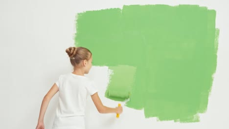 Niño-Pintando-La-Pared-Al-Color-Verde