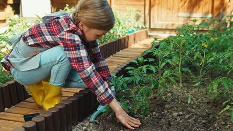 Niño-Plantando-Plántulas-De-Tomate-En-El-Jardín-Y-Sonriendo-A-La-Cámara