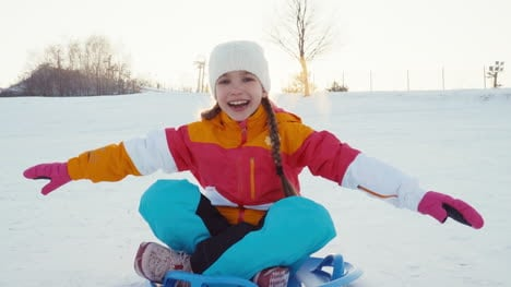 Child-Rides-A-Sledding-Down-A-Winter-Hill-At-Camera-Girl-Laughing