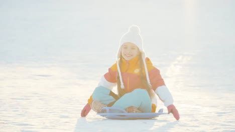 Child-Rides-A-Sledding-Down-A-Winter-Hill-Girl-Spinning-On-Snow-Disk