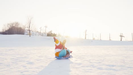 Laughing-child-rides-a-sled-down-on-snowy-hill