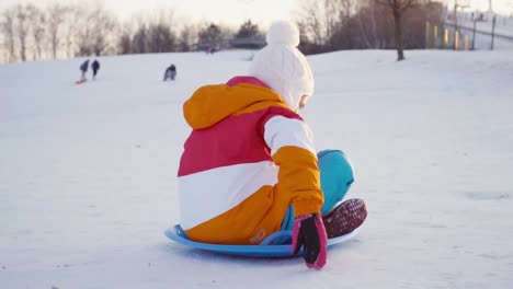 Child-Rides-A-Sledding-Down-On-Snow-Disk-A-Winter-Hill-At-Camera
