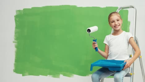 Child-Sitting-On-Ladder-Near-Green-Screen-Wall