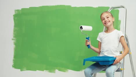 Child-Sitting-On-Ladder-Near-Green-Screen-Wall-Girl-Holds-Paint-Brush