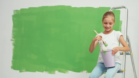 Child-Sitting-On-Ladder-Near-Wall-To-Green-Color-Girl-Holds-Paint-Brush