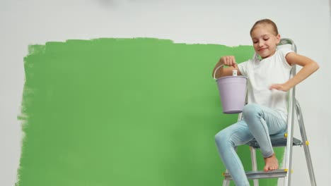 Child-Sitting-On-Ladder-On-The-Background-Of-Green-Screen
