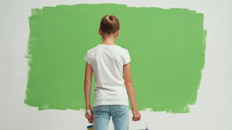 Child-Turns-Around-At-Camera-With-Bucket-Of-Paint-And-A-Brush-In-Her-Hand