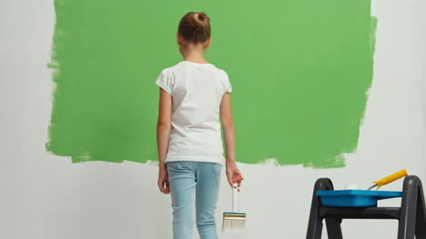 Niño-Turns-Around-With-Brush-In-Her-Hand-Near-Green-Collor-Wall