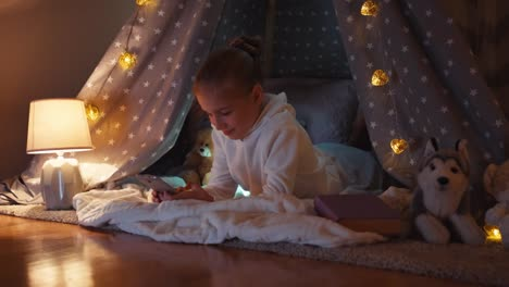 Child-Using-Cellphone-In-The-Wigwam-In-The-Night-In-The-Bedroom-And-Smiling