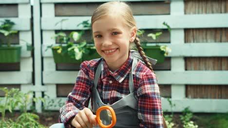 Kind-Mit-Lupe-Das-Auf-Die-Blume-Der-Tomate-Schaut-und-In-Die-Kamera-Lächelt