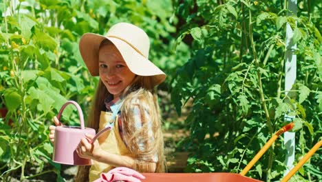 Child-Watering-Vegetables-In-Her-Kitchen-Garden-And-Smiling-At-Camera