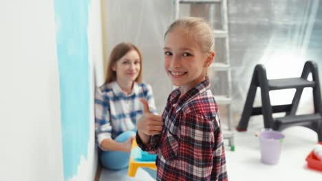 Child-With-Mother-Painting-Wall-To-Blue-Color-Thumbs-Up-Ok