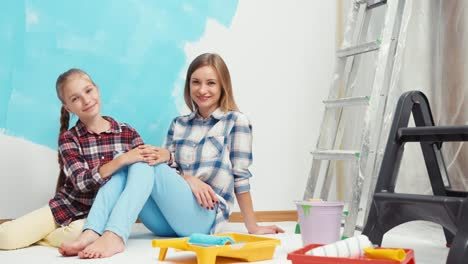 Child-With-Mother-Painting-Wall-To-Blue-Color-Zooming