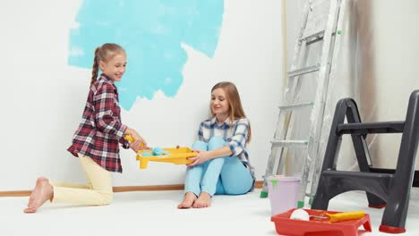 Child-With-Mother-Painting-Wall-To-Blue-Color