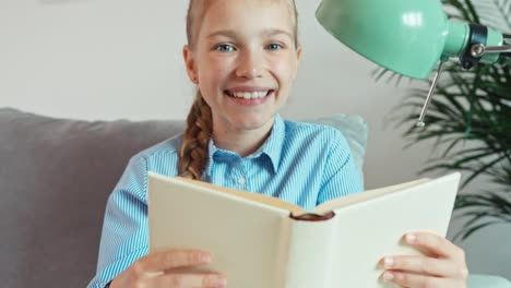 Close-Up-Portrait-Cheerful-Girl-9-Years-Old-Holds-In-Her-Hands-Book-And-Smiling