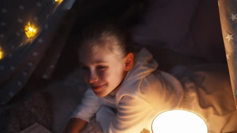 Close-up-of-cheerful-girl-reading-book-in-a-tent-in-her-room