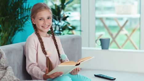 Close-Up-Portrait-Child-Reading-Book-In-The-Living-Room-And-Uses-Remote-Tv