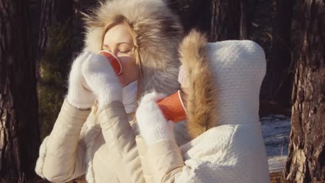 Close-Up-Portrait-Mother-And-Daughter-Drinking-Hot-Tea-In-Winter-Forest-Looking