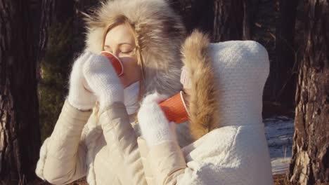 Retrato-De-Cerca-Madre-E-Hija-Bebiendo-Té-Caliente-En-El-Bosque-De-Invierno-Mirando