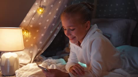 Close-Up-Shot-Girl-Using-Cell-Phone-In-Wigwam-In-The-Night-Smiling-At-Camera