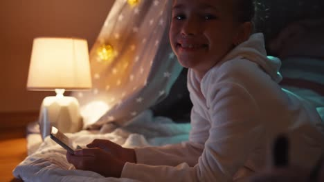 Closeup-Portrait-Child-Using-Cellphone-In-The-Wigwam-In-The-Night-In-The-Bedroom