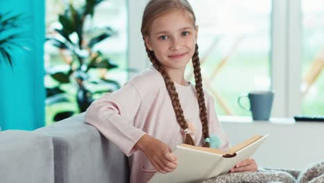 Closeup-Portrait-Girl-9-Years-Old-Reading-Book-In-The-Living-Room-And-Smiling